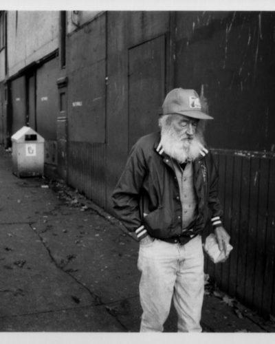 Elderly homeless man walking on sidewalk