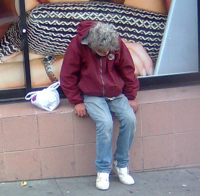 Photo of homeless man sitting on wall